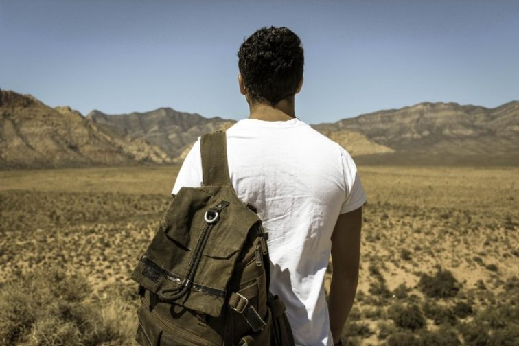 backpacker-standing-on-desert-and-looking-at-mountains