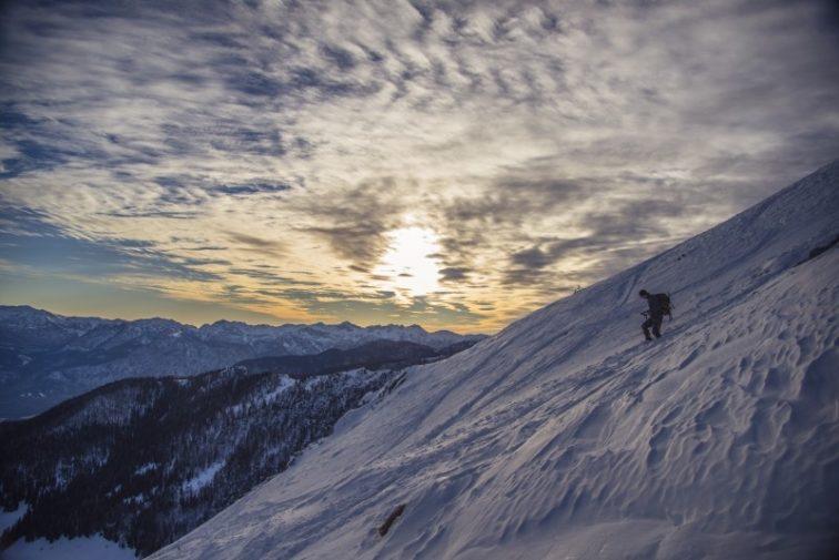 man-walking-down-mountain-in-winter