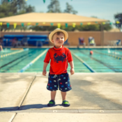 boy-standing-in-front-of-a-pool